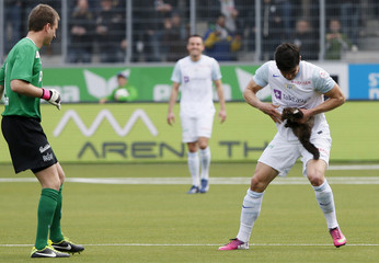 A marten bites FC Zurich's Benito as he attempts to remove the animal which was running on the pitch during the Swiss Super League soccer match against FC Thun in Thun