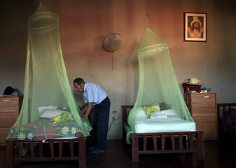 A man places a mosquito net  in a home for the elderly in Masaya City