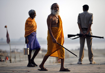 A Sadhu or a Hindu holy man walks past Indian security personnel on his way to cast vote at a polling station at Ayodhya