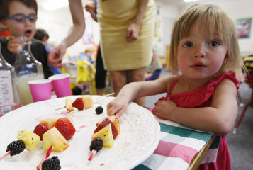 Kaylan Lessen, 2, a sibling of a student in the Lookout Mountain Preschool takes a fruit kabob at a school party for mother's day in Golden