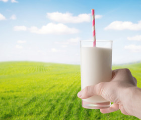 Glass of milk in hand on a natural background (first person view)