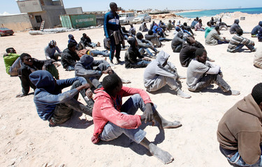 Migrants, who attempted to flee the Libyan coast to head to Europe, are seen seated on the ground after being detained at the coast guard center in the coastal city of Tripoli, Libya
