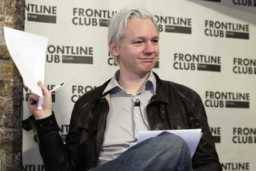 WikiLeaks founder Julian Assange holds a document containing leaked information at a news conference in London