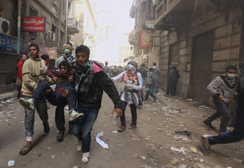 An injured Egyptian protester is carried during clashes with riot police along a road that leads to the Interior Ministry, near Tahrir Square in Cairo