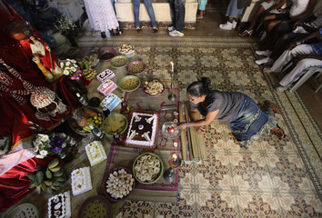 """A woman makes an offering at an altar during an initiation ceremony for new drummers in Afro-Cuban """"santeria"""" religion events in Havana"""