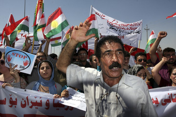 Residents wave Kurdish flags during a protest against Turkish and Iranian shelling on northern Iraqi, outside the United Nations headquarters in Arbil