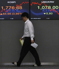 A foreign currency dealer of the Korea Exchange Bank walks by screens at the bank's dealing room in Seoul
