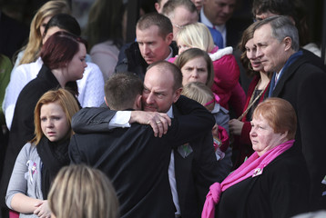Mourners hug each other as they file out of the Church of Jesus Christ of Latter-Day Saints after the funeral of Emilie Parker in Ogden