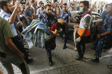 A Palestinian policemen carries a girl, who medics said was wounded in Israeli shelling, at a hospital in Gaza City