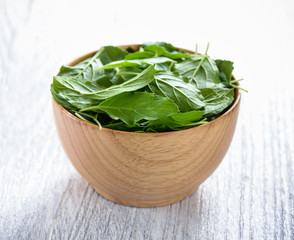 Basil leaves in a wooden bowl