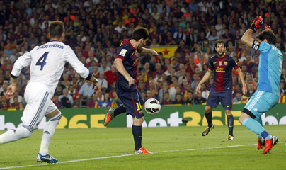 Barcelona's Messi shoots to score in front of Real Madrid's Casillas during their Spanish first division soccer match at Nou Camp stadium in Barcelona