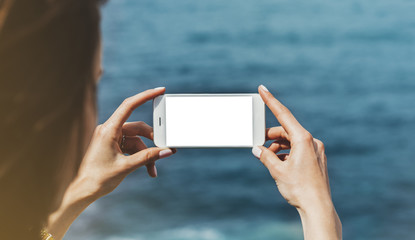 Hipster photograph on smart phone gadget mobile, mock up of blank screen. Traveler hold and using in female hand mobile on background mountain seascape horizon. Tourist look on blue ocean, lifestyle