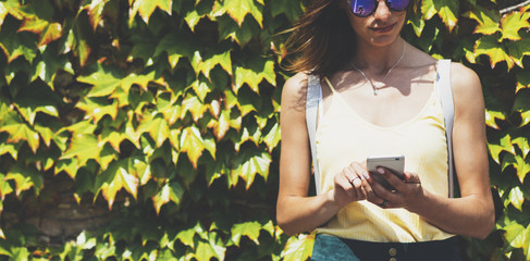 Fotomurales - Portrait young women in sunglasses using smart phone isolated on background green nature wall mock up, pretty hipster female hands text message holding mobile gadget, blurred summer backdrop