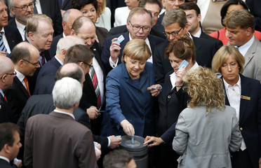 German Chancellor Merkel casts her vote during a session of the lower house of parliament Bundestag in Berlin