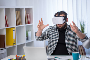 Future is now. Handsome young man in VR headset gesturing while sitting in creative office