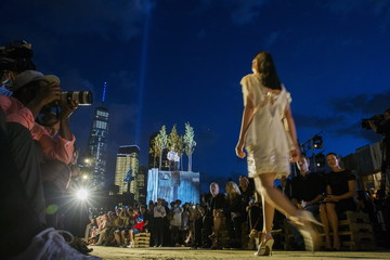 A model presents a creation from the Givenchy Spring/Summer 2016 collection, as the Tribute in Light installation shines next to One World Trade in the background, during New York Fashion Week in New York