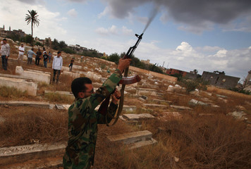 An anti-Gaddafi fighter fires in the air during the funeral of his comrades who were killed in Bani Walid, in Tripoli