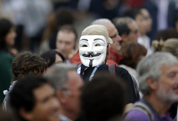 "A man wears a Guy Fawkes mask before the red carpet of the movie ""Apres mai "" at the 69th Venice Film Festival in Venice"