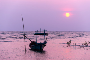 Small fishing boat at sunset in the sea