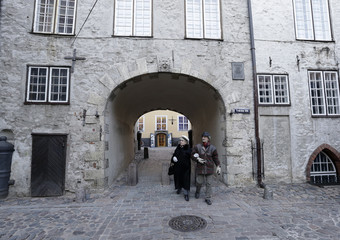 People walk through the Swedish Gate in the Old City of Riga