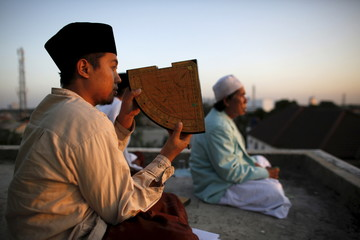 A Muslim man uses a traditional tool called a rubu to look at the position of the moon to mark the end of the holy month of Ramadan at Al-Musyari'in mosque in Jakarta