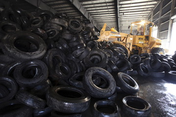 A worker uses a forklift to store abandoned tyres to remove potential breeding spots for mosquitoes transmitting Zika and other mosquito-borne diseases at a temporary collection center in San Juan