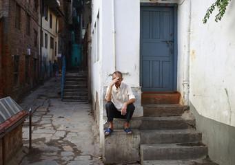 A man sits near the entrance of a house in Kathmandu