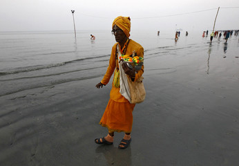 A Sadhu carries an idol of a Hindu deity as he walks along the confluence of the river Ganges and the Bay of Bengal ahead of the Makar Sankranti festival at Sagar Island