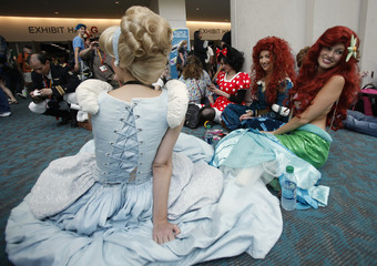 Girls wearing costumes sit on the floor during Comic Con International convention in San Diego