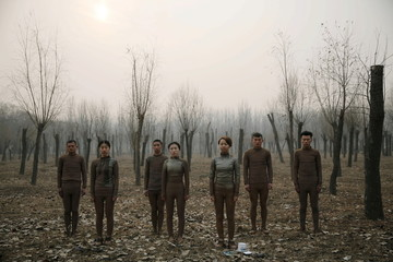 """Models pose before they are painted in camouflage colours to blend in with the background for Chinese artist Liu Bolin's artwork """"Dongji"""", or Winter Solstice, in Beijing"""