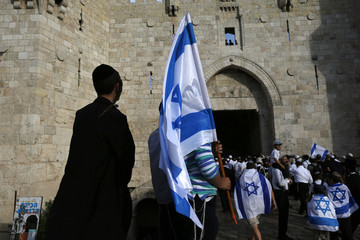 Israelis carry flags as they enter Jerusalem's Old City during a parade marking Jerusalem Day