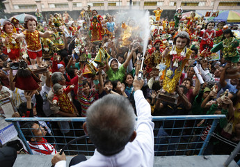 A lay minister sprays water to bless a crowd of devotees carrying statues of the Sto. Nino during the Feast of Sto. Nino in Manila