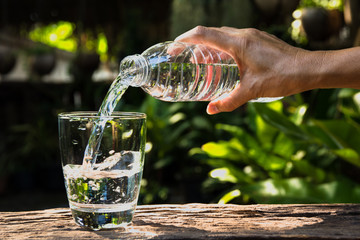Female hand pouring water from bottle to glass on nature background