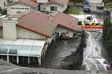 Crews work to channel mudflows in the area of lthe 2013 Springs Fire, in Camarillo, California