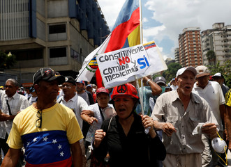 An elderly opposition supporter carries a sign during a rally against President Nicolas Maduro in Caracas