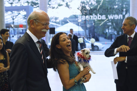 Daimler CEO Zetsche laughs with a woman holding a dog during a gala celebrating the opening of a new Mercedes-Benz dealership in New York