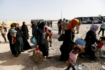 Civilians who fled their homes due to clashes gather at Camp Tariq, south of Falluja