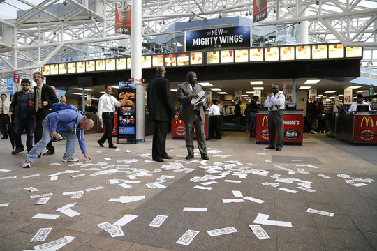 Protest fliers cover the floor after a rally in support of higher pay for low-wage earners at the National Air and Space Museum in Washington