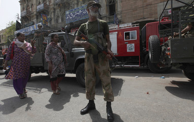 Women walk past a paramilitary soldier, standing guard along a road outside the district city court, in Karachi