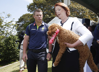 Australia's Prime Minister, Gillard holds her dog Reuben as she poses for photographers with Australian cricketer Warner at afternoon tea at Kirribilli House in Sydney