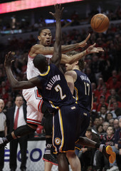 Bulls' Rose passes around Pacers' Collison and Dunleavy during the first half of Game 1 of their NBA Eastern Conference first round playoff basket ball game in Chicago