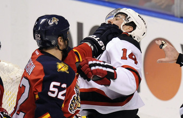 Florida Panthers Jason Garrison hits New Jersey Devils Adam Henrique during the third period of their NHL Eastern conference quarterfinal playoff hockey game 2 in Sunrise