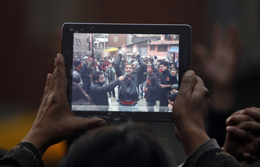 Man records Shi'ite Muslims taking part in a protest against Israel's military action in Gaza, on his iPad in Srinagar