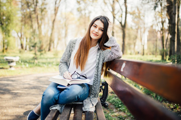 beautiful university student reading at the park on bench