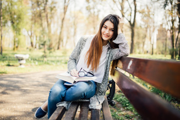 The girl sitting on a bench, reading a book sunny day