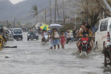 People walk through a flooded street in the aftermath of super typhoon Haiyan in Tacloban