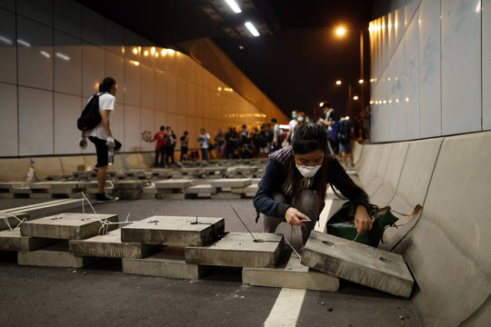 A pro-democracy protester lays bricks inside a vehicle tunnel to block traffic leading to the financial Central district in Hong Kong