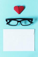 Glasses in dark frame, white blank envelope and red heart of origami