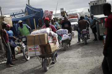 Haitians cross the border between Haiti and the Dominican Republic carrying goods bought in the Dominican Republic, in Malpasse