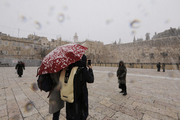 A woman has her picture taken as snow falls near the Western Wall in Jerusalem's Old City